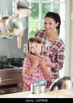 Woman hugging daughter in kitchen - Stock Photo