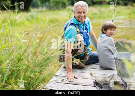 Man fishing with grandson on wooden dock - Stock Photo