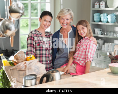 Three generations of women in kitchen - Stock Photo