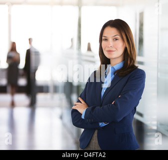 Businesswoman standing in office hallway - Stock Photo