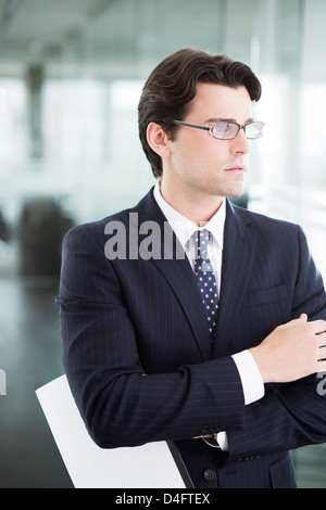 Businessman standing in office hallway - Stock Photo