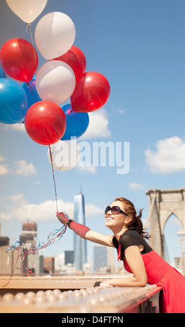Woman holding bunch of balloons on urban bridge - Stock Photo