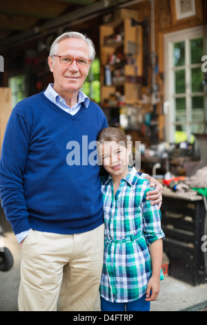 Man and granddaughter smiling in garage - Stock Photo