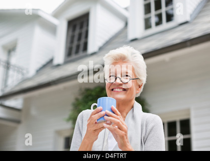 Woman having cup of coffee outdoors - Stock Photo
