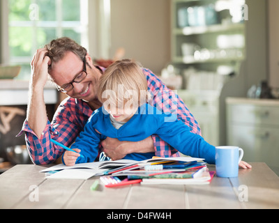 Father and son doing homework at kitchen table - Stock Photo