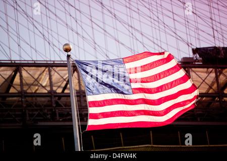 American flag waving by urban bridge - Stock Photo