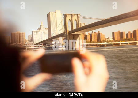 Hands taking picture of urban bridge and cityscape - Stock Photo