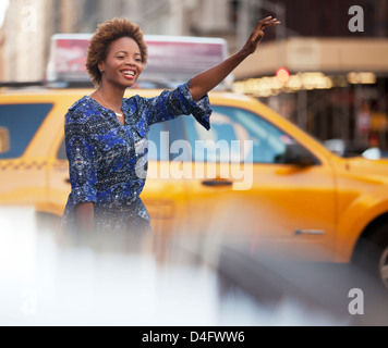 Woman hailing taxi on city street - Stock Photo