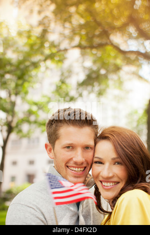 Couple waving American flag in urban park - Stock Photo