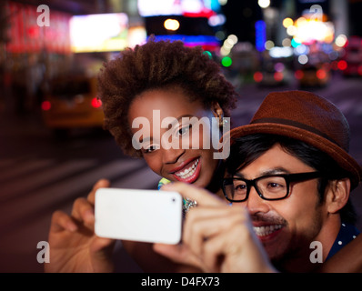 Couple taking pictures on city street - Stock Photo