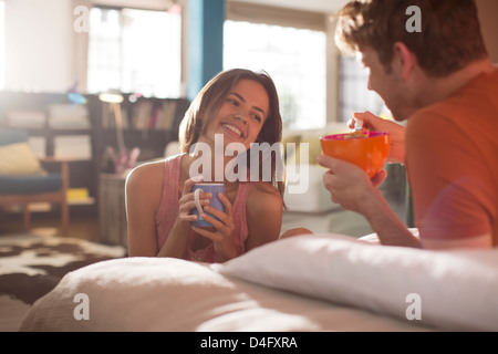 Couple having breakfast in bed together - Stock Photo