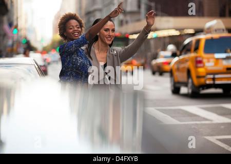 Women hailing taxi on city street - Stock Photo