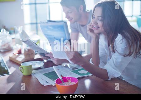 Couple reading magazines at breakfast - Stock Photo