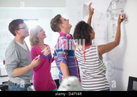 Business people reading blueprints in office - Stock Photo