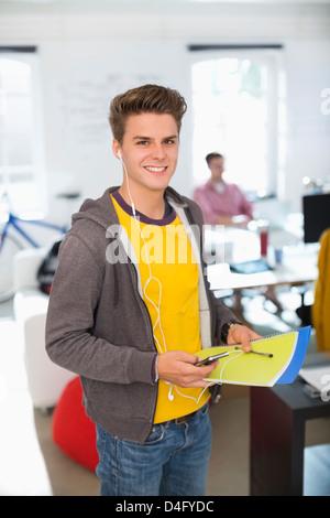 Man wearing headphones in office - Stock Photo