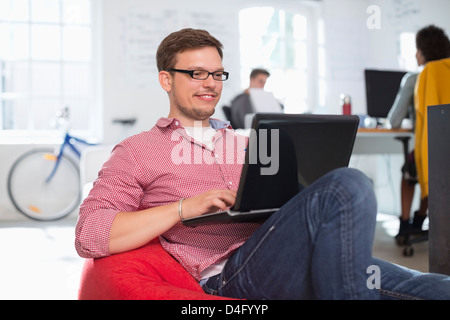 Businessman using laptop in bean bag chair in office - Stock Photo