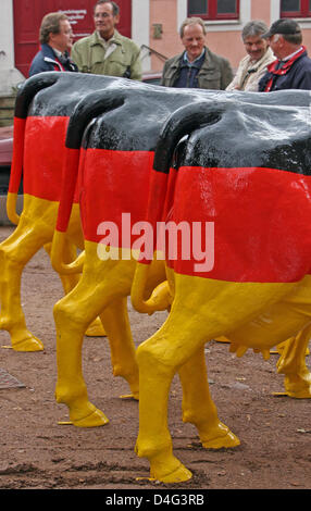 Plastic cows painted in the German national colours and with the inscription 'Die faire Milch' (literally: the fair - Stock Photo