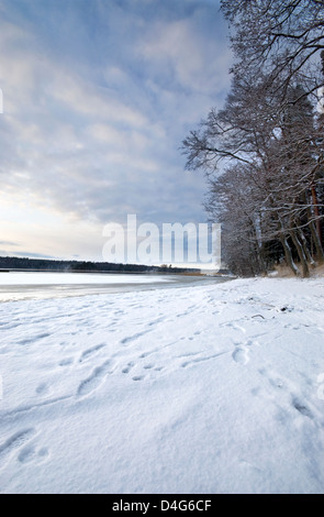 Winter scene with a thick pack of snow and a frozen bay in southern Finland - Stock Photo