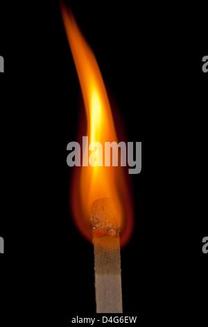 Flame burning on match against black background. - Stock Photo