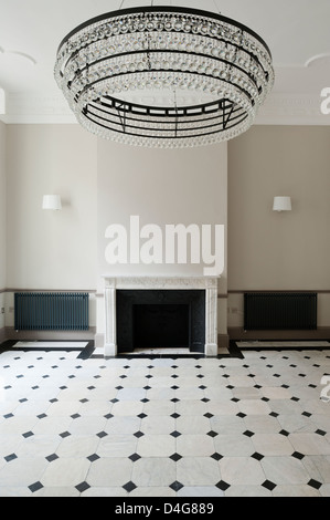 empty room with large chandelier and fireplace - Stock Photo