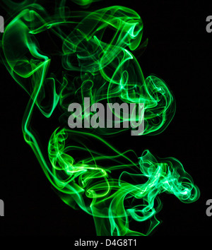 Smoke painted by green light forming an abstract figure - Stock Photo