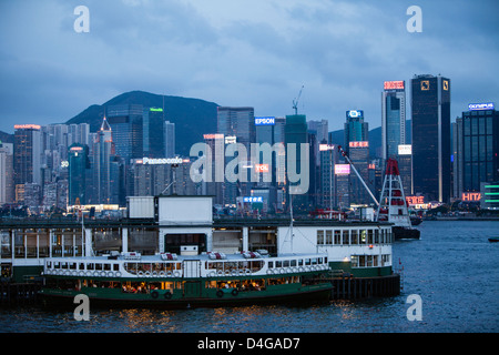 Star Ferry at the Kowloon Terminal, on Victoria Harbour with Hong Kong skyline in the  background. - Stock Photo