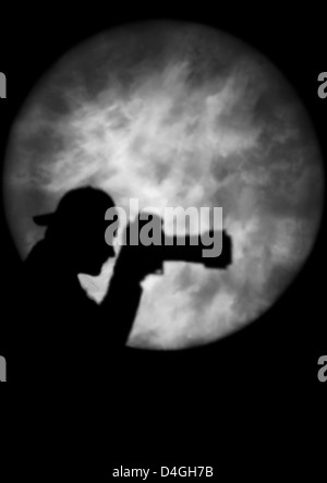 Silhouette of a man holding a camera in spotlight or moonlight (model released) - Stock Photo