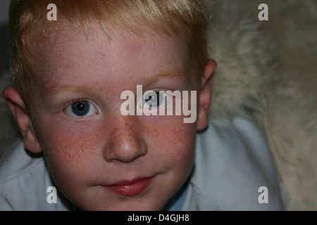 A young boy sitting on a sheepskin rug looking up into the camera - Stock Photo