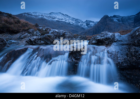 Fairy Pools waterfalls at Glen Brittle, with the snow dusted Cuillin mountains beyond, Isle of Skye, Scotland. - Stock Photo