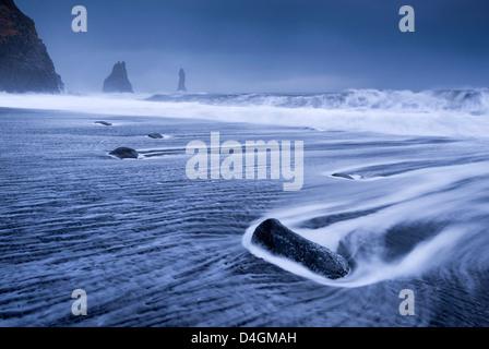 Waves rushing over black sand beach near Vik on the South coast of Iceland. Winter (January) 2013. - Stock Photo
