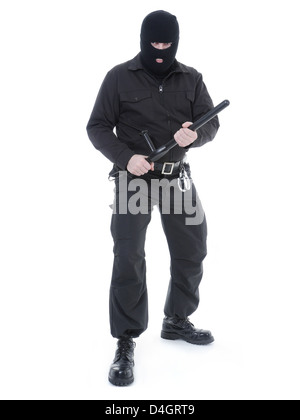 Antiterrorist police guy wearing black uniform and black mask holding firmly police club in both hands ready for - Stock Photo