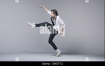 Handsome young man in acrobating pose - Stock Photo