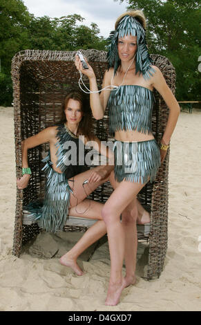 Models Vera Gafron (L) and Franziska Scheffer enjoy themselves during the presentation of the new beach fashion - Stock Photo