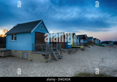 Beach huts on Mudeford Spit at Hengistbury Head near Christchurch just after sunset. - Stock Photo