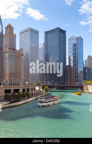 Tourist boat on the Chicago River with glass towers behind on West Wacker Drive, Chicago, Illinois, USA - Stock Photo