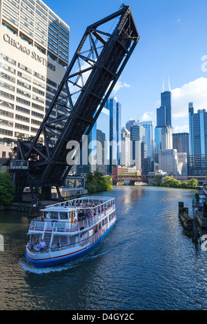 Tour boat passing under a railway bridge on the Chicago River, Downtown towers in the background, Chicago, Illinois, - Stock Photo