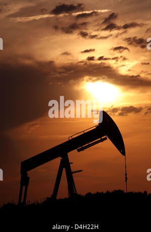 The sun sets behind a pumpjack-type oil pump near Emlichheim, County Bentheim, Germany, 28 July 2008. Since 60 years Kassel-based energy provider 'Wintershall' has been producing oil in the border region to the Netherlands. 150,000 tons of oil are conveyed per year. Photo: Uwe Zucchi
