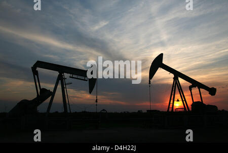 The sun sets behind two pumpjack-type oil pumps near Emlichheim, County Bentheim, Germany, 28 July 2008. Since 60 years Kassel-based energy provider 'Wintershall' has been producing oil in the border region to the Netherlands. 150,000 tons of oil are conveyed per year. Photo: Uwe Zucchi