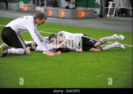 Germany's Piotr Trochowski (C) celebrates scoring the 1-0 with his team-mates Per Mertesacker (L) and Bastian Schweinsteiger - Stock Photo