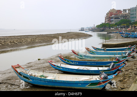 Sampan style fishing boats moored on the shoreline of the Tamsui River estuary at low tide, Tamsui (Danshui), Taiwan - Stock Photo
