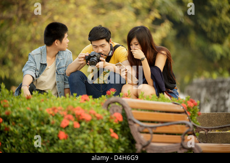 Three people sitting in park, one is  watching the photos on camera, Bangkok, Thailand - Stock Photo