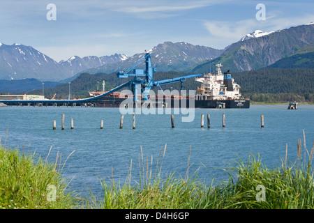Bulk freighter ('bulker') being loaded with coal via conveyor belt, Resurrection Bay, Seward, Alaska, USA, late - Stock Photo