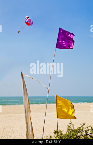 vertical colorful flags blowing in breeze sand sea tropical para glider glides by at Uttorda Beach Goa India - Stock Photo