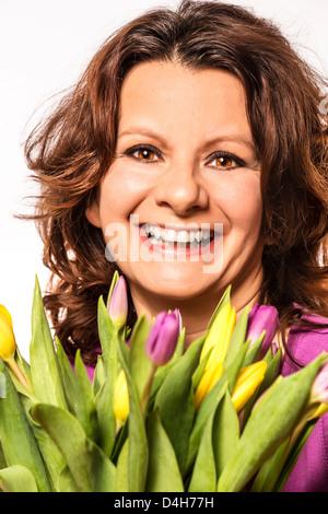 Beautiful brunette woman enjoying a bouquet of flowers - Stock Photo
