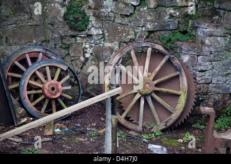 cart wheels, wooden, weathered, old circular saw blade, rusted,decrepit, against old stone wall - Stock Photo