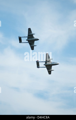 Portrait image of two small jet aircraft flying in close formation, seen from below. - Stock Photo