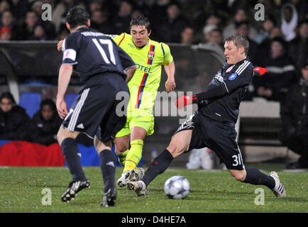 Anthony Mounier (C) of Olympique Lyon vies for the ball with FC Bayern Munich players Mark van Bommel (L) and Bastian - Stock Photo