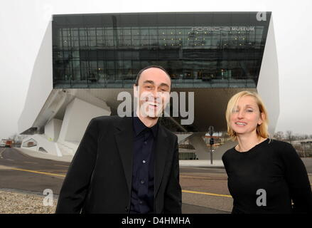 Architects Roman Delugan (L) and his wife and business partner Elke Delugan-Meissl (R) pose outside the building they designed during the inauguration of the new Porsche museum in Stuttgart, Germany, 28 January 2009. The futuristic building was inaugurated after three years of construction and will be opened for visitors on 31 January. A total of 82 of Porsche?s most relevant model Stock Photo