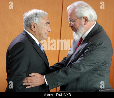 Director of the International Monetary Fund (IMF), Dominique Strauss-Kahn (L), chats with the General Director of - Stock Photo