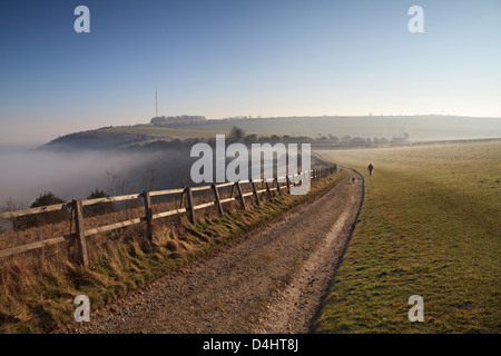 A walker on the Wayfarer's Walk at Cannon Heath Down, Hampshire with Hannington TV mast on Cottington Hill in the - Stock Photo